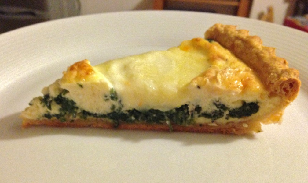 Slice of Spinach tart topped with goats cheese / mozzarella